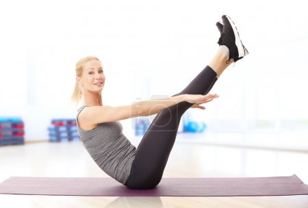 woman sitting at pilates mat