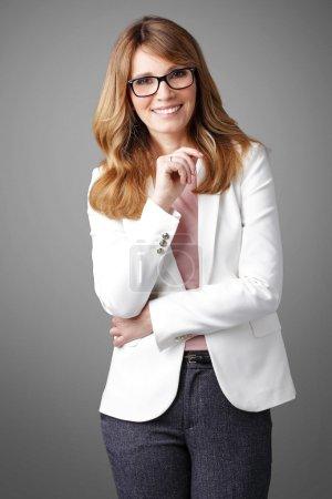 Photo pour Portrait de souriante femme d'affaires attrayante debout à l'arrière-plan isolé . - image libre de droit