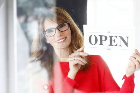 Photo for Portrait of middle aged woman holding an open sign while standing at her store. - Royalty Free Image