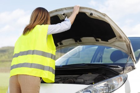 woman standing at her broken down car