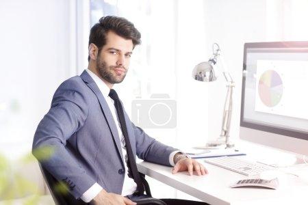 Photo pour Portrait d'un bel assistant financier assis sur son lieu de travail et travaillant sur ordinateur . - image libre de droit
