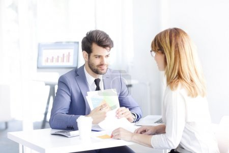 Photo pour Portrait of young investment advisor professional man holding in his hands financial plan while consulting with executive businesswoman. - image libre de droit