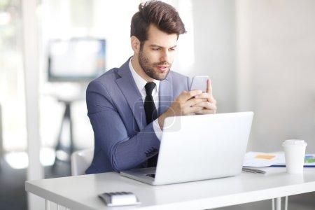 Photo pour Portrait d'un jeune homme d'affaires utilisant un téléphone portable et un ordinateur portable alors qu'il était assis au bureau et travaillait dans un rapport financier . - image libre de droit