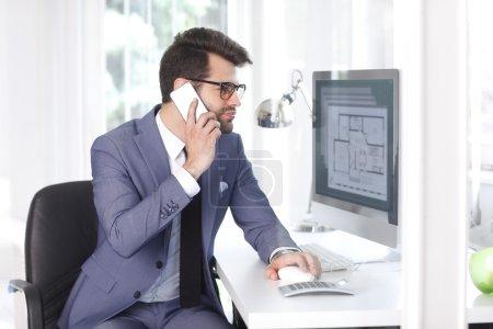 Photo pour Portrait d'une jeune conseillère financière exécutive faisant un appel alors qu'elle était assise au bureau devant un ordinateur . - image libre de droit