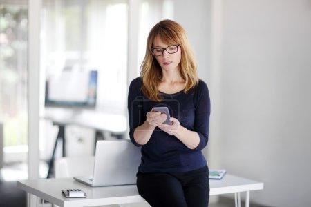 Photo pour Portrait d'une vendeuse confiante utilisant son téléphone portable debout au bureau . - image libre de droit
