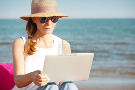 Photo for Portrait of beautiful middle aged woman using her laptop and working online while sitting on the beach. - Royalty Free Image