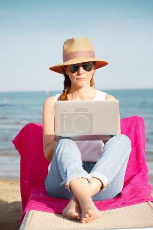 Photo pour Portrait complet d'une femme d'affaires occasionnelle travaillant au bord de la mer pendant les vacances d'été. Femme d'âge moyen assise sur un transat au bord de la mer et tapant sur son ordinateur portable . - image libre de droit