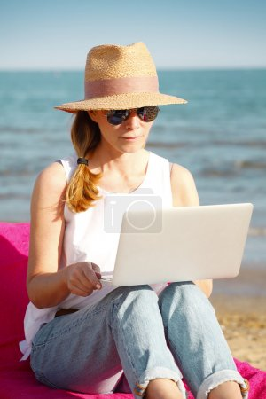 Photo for Portrait of middle aged woman using her laptop while sitting on sunbed on the seaside. - Royalty Free Image