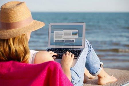 Photo pour Vue arrière d'une femme utilisant son ordinateur portable et assise sur la plage . - image libre de droit