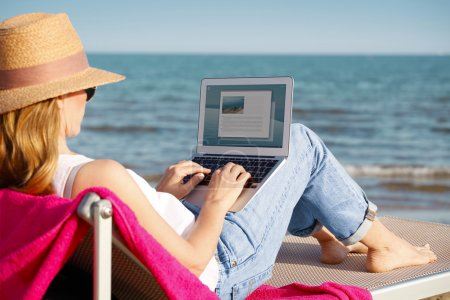 Photo for Rear view shot of a woman using her laptop and while sitting on beach. - Royalty Free Image