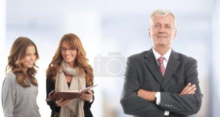 Photo pour Homme d'affaires senior permanent avec ses collègues de bureau. Travail d'équipe. - image libre de droit