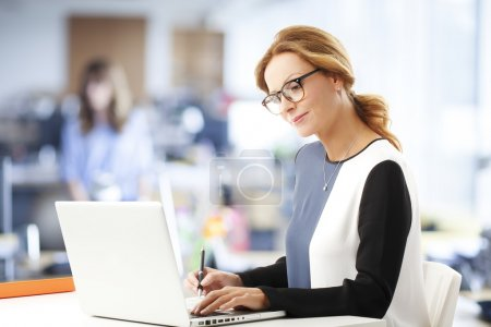Photo pour Financial assistant working on laptop while sitting at office. - image libre de droit