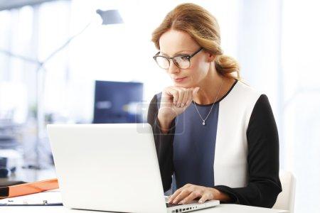 Photo pour Femme d'affaires confiante qui travaille sur un ordinateur portable et écrit sa présentation - image libre de droit