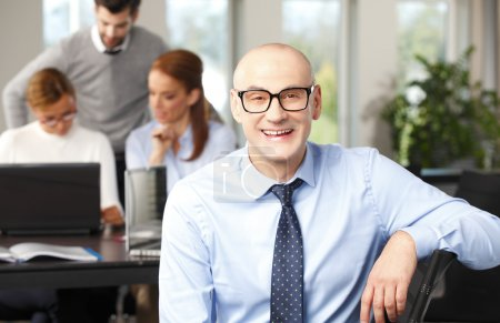 Photo pour Gros plan du dirigeant principal des finances assis au bureau avec ses collègues . - image libre de droit