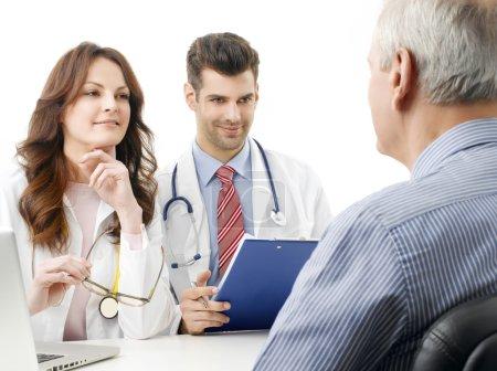 Photo pour Portrait d'une équipe médicale qui consulte un patient âgé. Isolé sur fond blanc . - image libre de droit