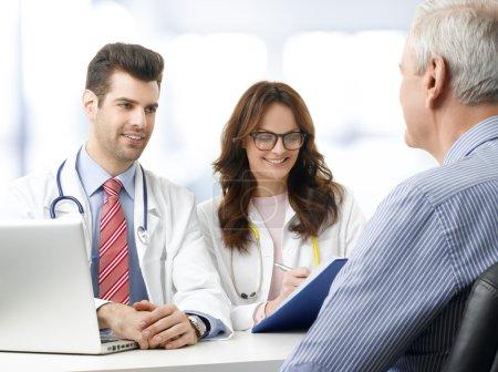 Photo pour Médecin féminin et médecin masculin consultant à partir des résultats des tests médicaux avec le patient âgé à la maison de soins infirmiers - image libre de droit