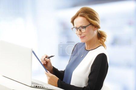 Photo pour Portrait de femme d'affaires analysant les données tout en tenant presse-papiers dans ses mains . - image libre de droit