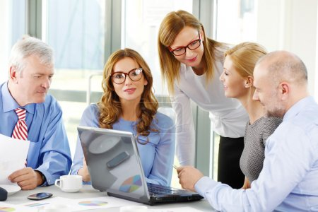 businesswomen and businessmen around conference table