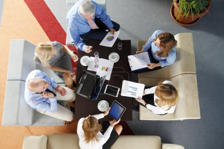 Photo for Image from above of business people sitting around the desk and working on presentation. Teamwork at office. - Royalty Free Image
