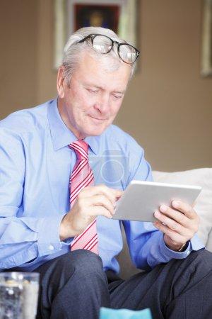 Senior man sitting holding tablet