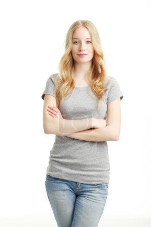 Photo pour Portrait de belle jeune femme avec les bras croisés debout sur fond blanc tout en regardant la caméra et en souriant . - image libre de droit