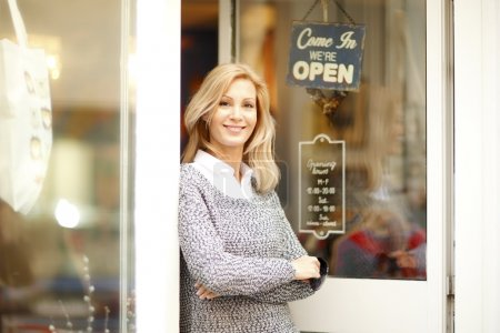 Photo for Portrait of attractive clothing store owner standing in her shop entrance. Small shop owner looking at camera and smiling. - Royalty Free Image
