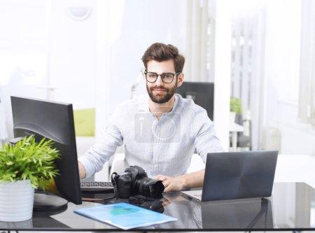 Photo pour Portrait de jeune directeur artistique travaillant à son bureau. Propriétaire d'un studio de design graphique assis au bureau devant un moniteur et un ordinateur portable et travaillant en ligne . - image libre de droit