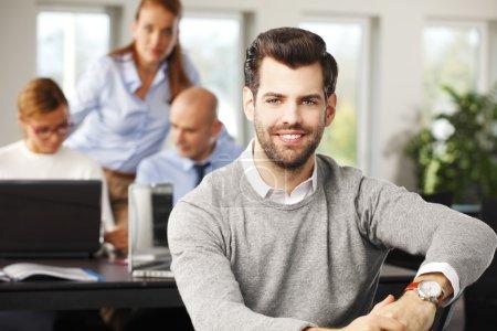 Photo pour Portrait de jeune courtier assis au bureau et regardant la caméra. Experts financiers travaillant à l'ordinateur en arrière-plan . - image libre de droit