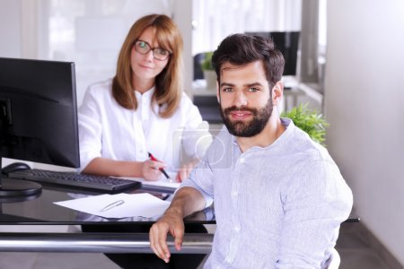 Photo pour Close-up portrait of young businessman sitting at office desk while mature sales woman sitting in front of personal computer and looking and camera. Business people working together at office. - image libre de droit