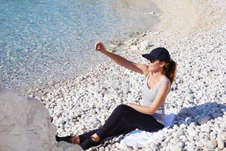 Photo pour Portrait pleine longueur d'une femme en forme assise sur la plage de galets après la course du matin et prenant autoportrait avec téléphone portable . - image libre de droit