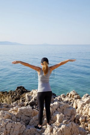 Fit woman with arms raised by sea