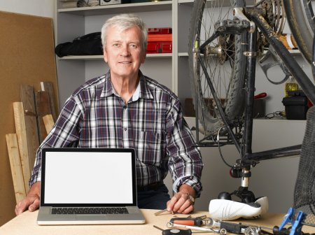 senior bike shop owner with laptop