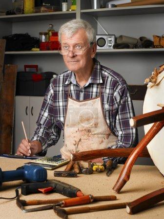 senior carpenter working at his worshop