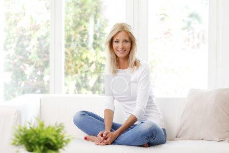 Photo pour Portrait de la belle femme mûre, souriant tout en étant assis sur le canapé à la maison. - image libre de droit