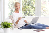 Woman sitting at sofa in front of laptop