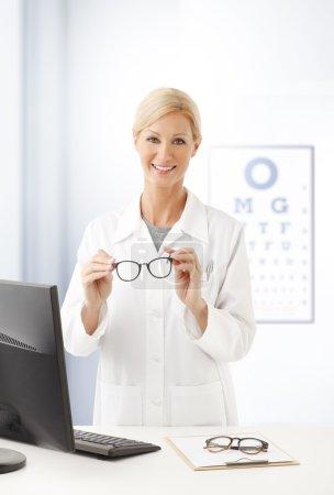 female doctor holding eyewear