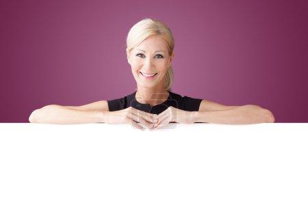 businesswoman leaning on billboard