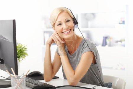 Photo pour Portrait d'un beau représentant de la clientèle avec casque souriant lors d'une conversation téléphonique - image libre de droit