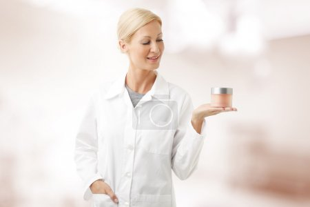 Beauty specialist holding bowl of cream