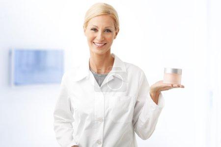 beauty therapist holding jar of cream