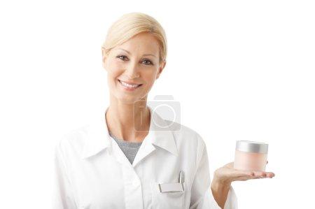 beauty therapist holding hand jar of cream