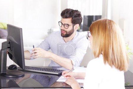 Photo pour Portrait d'un jeune conseiller en placement travaillant au bureau et consultant une femme d'affaires du nouveau projet. - image libre de droit