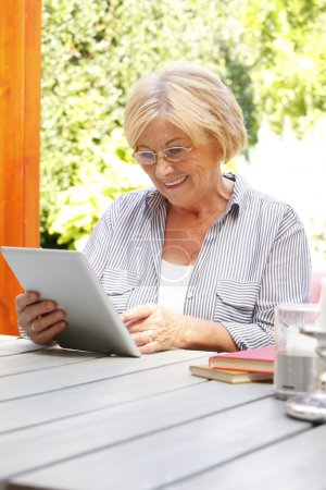 Retired woman holding tablet