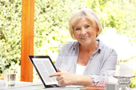 retired woman at garden using ebook reader