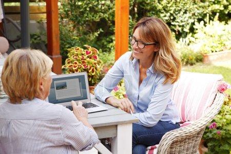 Photo pour Portrait de conseiller en placement consultant avec une retraitée à la maison. Conseiller d'affaires analysant des figures financières tout en s'asseyant devant l'ordinateur portatif avec la femme aînée. - image libre de droit