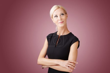 Photo for Portrait of beautiful businesswoman with arms crossed standing at isolated background while looking up and smiling. - Royalty Free Image