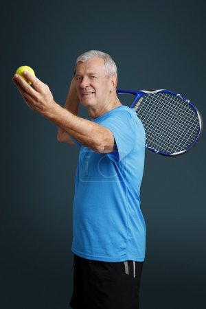Senior holding in hand a tennis racket