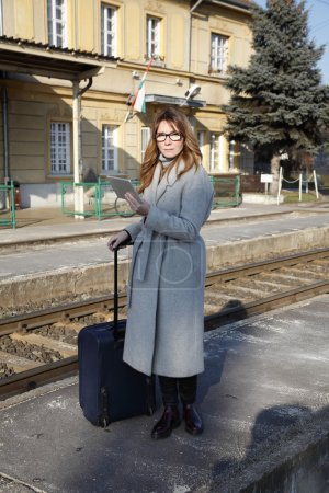 Photo for Full length portrait of middle age businesswoman holding  digital tablet and checking timetable while waiting for the train at the station. - Royalty Free Image