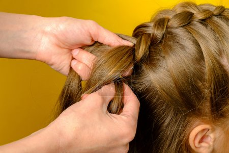 Mother braiding French braid her daughter