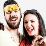 Постер, плакат: Thrilled couple taking mobile photographs and selfies
